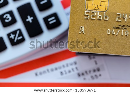 a gold credit card, bank statement and calculator. symbolic photo for cashless transactions and status symbols. - stock photo