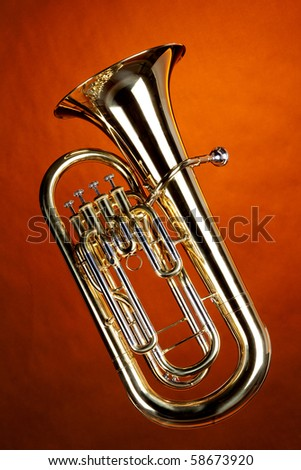A gold Euphonium tuba baritone horn isolated against an orange background in the vertical format. - stock photo