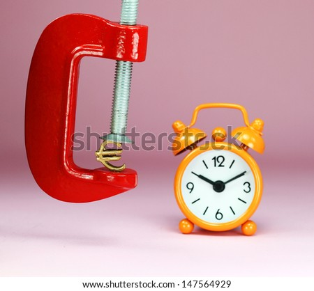 A Gold Euro Symbol in a red vice, with an orange clock with a pastel pink background, asking the question how far will the Euro be squeezed. - stock photo