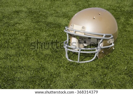 A gold football helmet resting on the turf. - stock photo