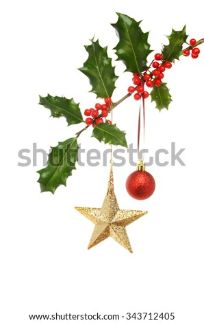 A gold glitter Christmas star and red bauble hanging from a holly branch with ripe red berries