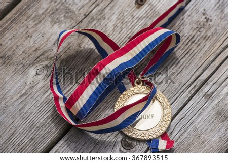 A gold medal with a red, white and blue ribbon on a wood surface. - stock photo