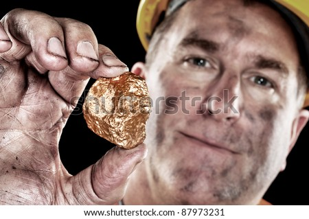 A gold miner shows a golden nugget freshly excavated from a mine. - stock photo