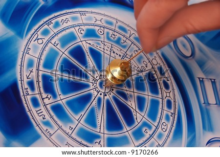 a gold pendulum in a female hand above an astrological wheel - stock photo