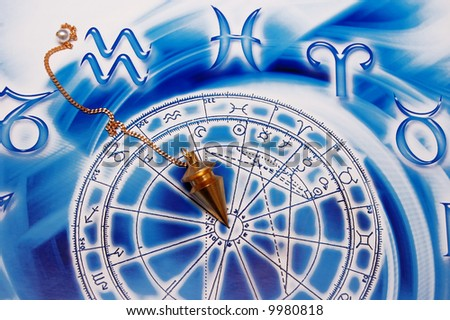 a gold pendulum lying on beautiful blue astrological background
