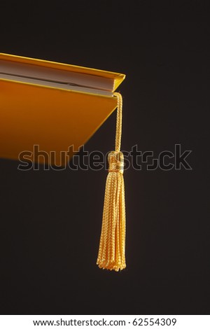 A gold tassel hanging out of a hard cover book on the black background metaphor for Graduation Cap - stock photo