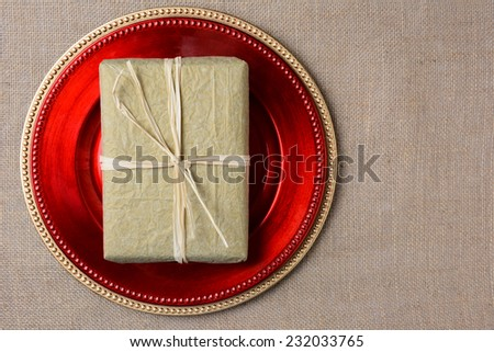 A gold tissue paper wrapped Christmas present on a red charger. The present is tied with raffia and both items are on a burlap surface. High angle shot in horizontal format with copyspace. - stock photo