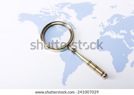 A gold vintage(classic, old) magnifier(reading glass) focus in america on the blue world map. - stock photo
