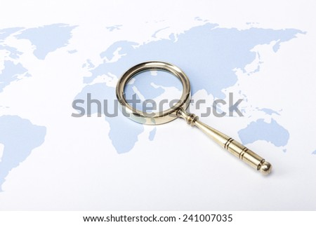 A gold vintage(classic, old) magnifier(reading glass) focus in arabia on the blue world map. - stock photo