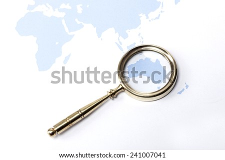 A gold vintage(classic, old) magnifier(reading glass) focus in Australia on the blue world map. - stock photo