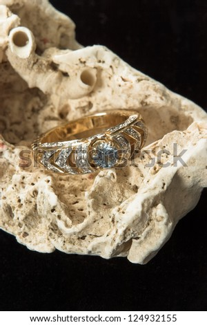 A gold wedding ring with white and blue diamonds on a type of coral. - stock photo