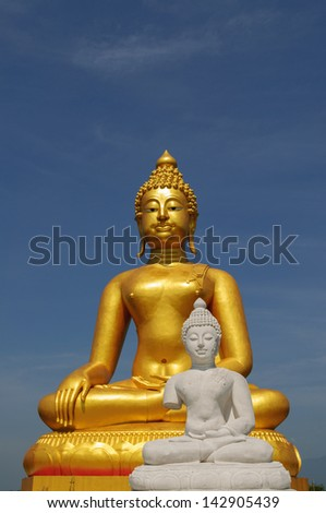 A golden and white buddha statue sits in peaceful meditation
