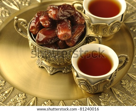 A golden bowl of dates and tea - stock photo
