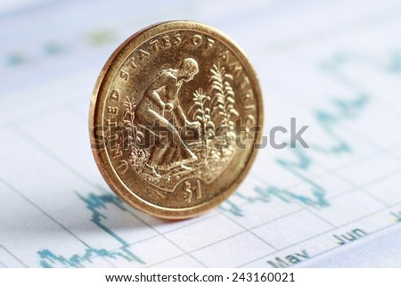 A golden coin on diagram papers, e-commerce - close-up - stock photo