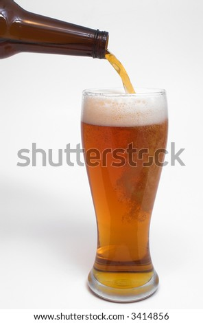 A golden colored beer being poured into a pilsner glass.