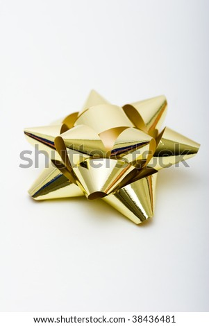 A golden colored gift bow isolated against white - stock photo