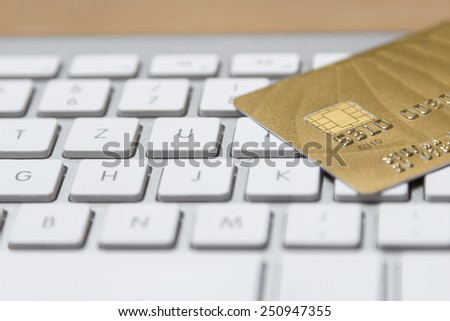 a golden credit card on a modern silver keyboard - stock photo