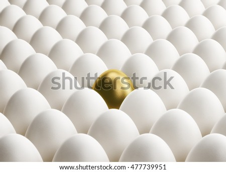 A golden egg is standing out from white eggs in multiple rows.