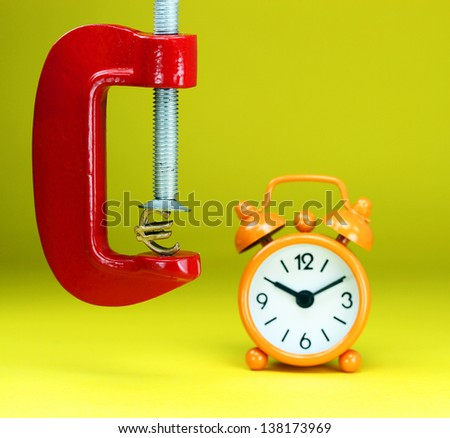 A golden Euro symbol placed in a red clamp with a pastel yellow background, with an orange  alarm clock in the background, indicating the pressure on pound. - stock photo