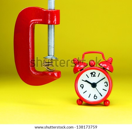A golden Euro symbol placed in a red clamp with a yellow background, with a red alarm clock in the background,  indicating the pressure on pound. - stock photo