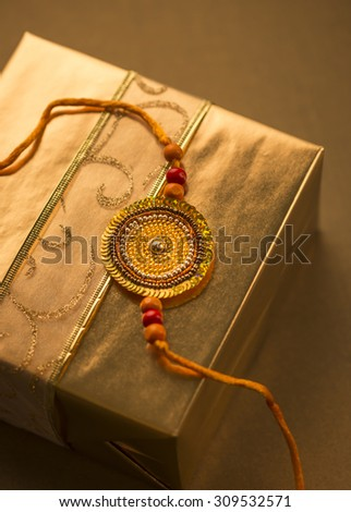 A golden gift pack with Rakhi string, - stock photo