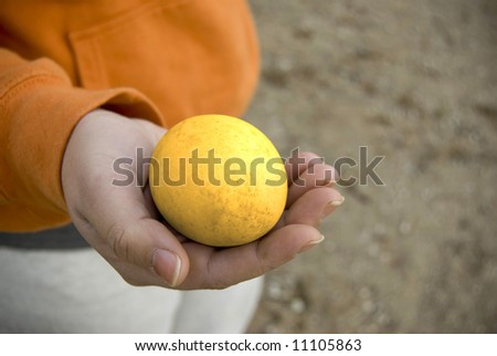 A golden goose egg in hand. - stock photo