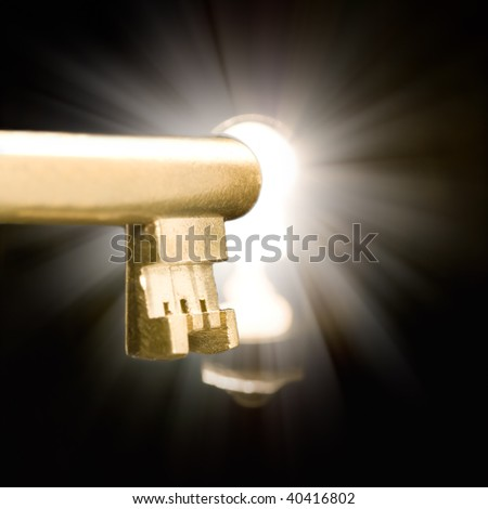 A golden key in a keyhole illuminated by a mysterious light - stock photo