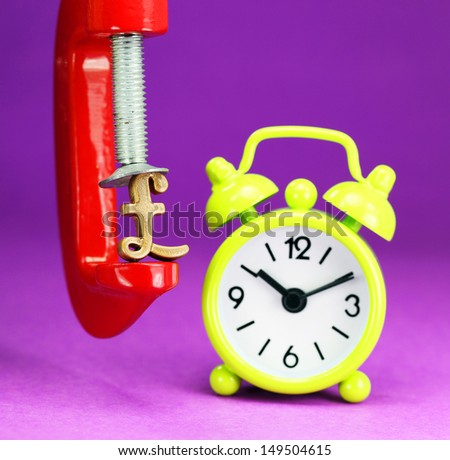 A golden pound symbol placed in red clamp with a yellow clock in the background, indicating the clock is ticking in the currency market. - stock photo