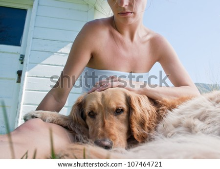 A golden retriever rests on the lap of it's owner, photo taken outdoors, slightly toned/Serious photo of dog and companion/Best friends - stock photo