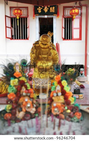 A Golden Statue of Budai or The Happy Buddha at a Shrine outside the Chinese Taoist Guan Di Gong Temple in Singapore - stock photo