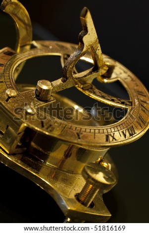 A golden sun dial combined with a compass. - stock photo