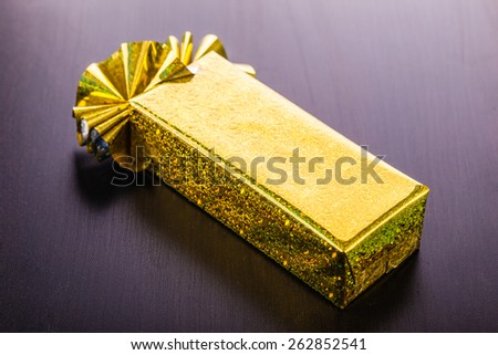 a golden wrapped gift box on a dark wooden surface - stock photo