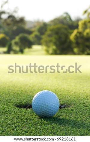A golf ball and hole at sunset. Golf tee and golf ball. - stock photo