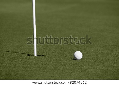 A golf ball approaches and stops near to the hole on the green.