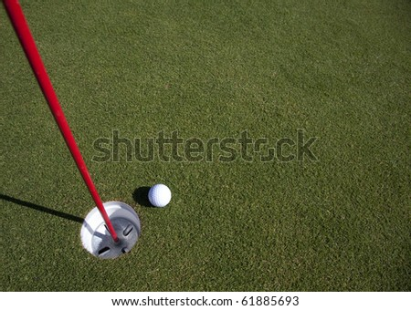 A golf ball comes to rest near the hole - with copyspace in the green - stock photo