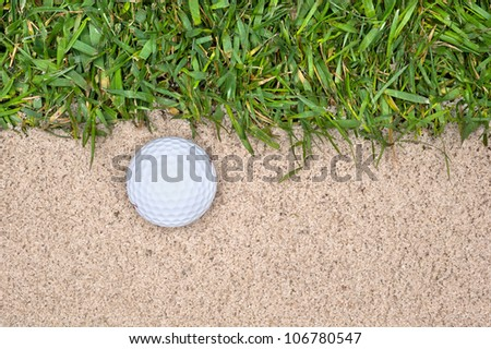 A golf ball in a sand trap next to the rough highlights the mistakes one can make playing the game.