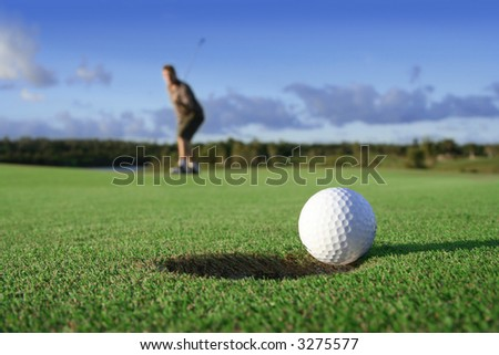 A golf ball just about to go in the hole from a long putt - stock photo