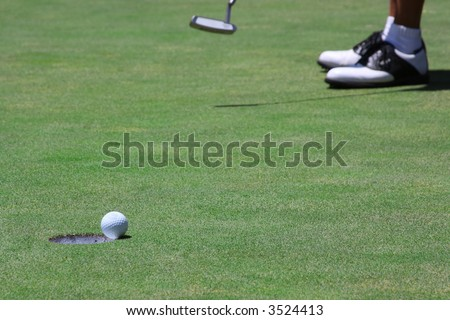 A golf ball just about to go into the hole from a long putt with selective focus on the ball - stock photo