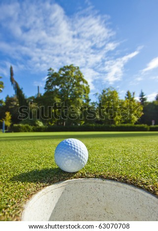 A golf ball just as it drops into the cup on a beautiful day - stock photo