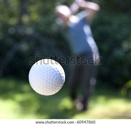 A golf ball just coming off the tee from a golfer in swing. - stock photo