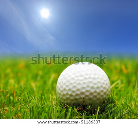 A golf ball on a green grass and a blue sky - stock photo