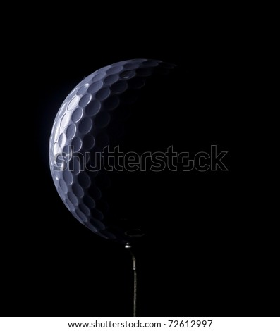 A golf ball on a tee, in dramatic black and white - stock photo
