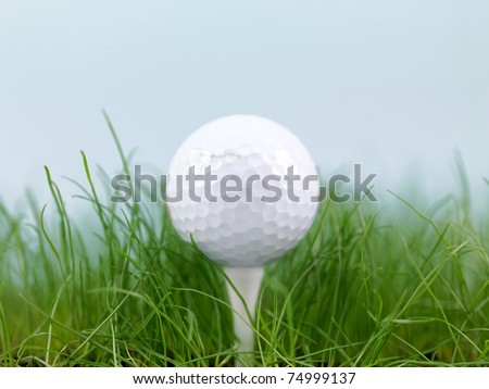 A golf ball on green grass isolated against a blue sky - stock photo