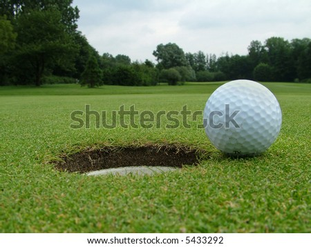 A Golf Ball on the edge of the hole