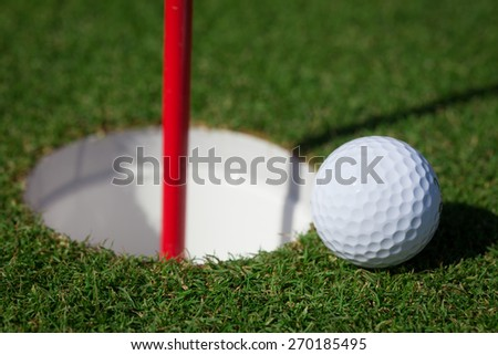 A golf Ball rests near the hole in a golf course - stock photo