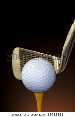 A golf ball seated on a wooden tee with a soft-focused iron club head in the immediate background.