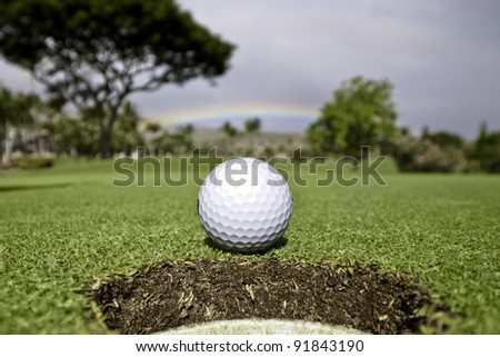 A golf ball sits at the lip of the hole with trees and rainbow in the background.