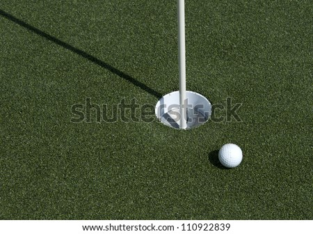 A golf ball sits near the hole on the putting green - stock photo