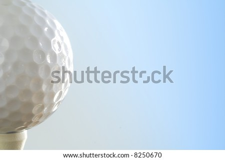 a golf ball teed up isolated against blue - stock photo