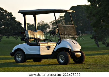 A golf cart sits on the fairway of a golf course at a private country club.